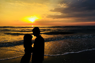 A couple in love are kissing against the sunset