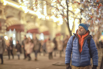 hipster santa in the city night / a young guy with a beard travels around Europe new year and Christmas