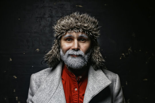 brutal man with a beard in winter clothes / portrait person with a gray beard, hipster warm clothes winter