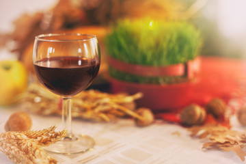 Wine glass with Christmas wheat and offerings, background