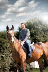 Smiling rider man on horse
