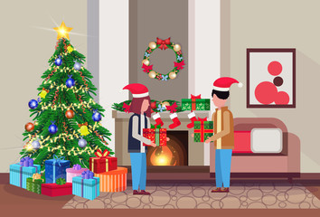 merry christmas happy new year couple give each other present gift box in living room pine tree fireplace home interior decoration winter holiday concept flat horizontal