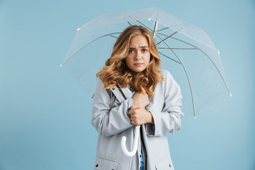 Image of displeased woman 20s wearing raincoat standing under transparent umbrella, isolated over blue background