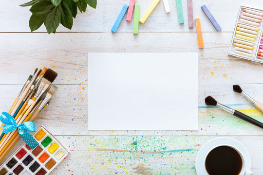 Paint brushes, paintbox with watercolors, crayons, coffee and blank mock up paper on white wooden background, artistic backdrop, creative artist studio, Top view from above, flat lay with copy space