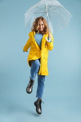 Full length image of young woman 20s wearing yellow raincoat standing under transparent umbrella, isolated over blue background