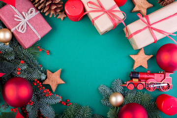 Christmas composition. Christmas green decorations, fir tree branches with toys gift boxes on green background. Flat lay, top view, copy space