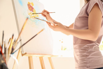Female artist painting picture in workshop