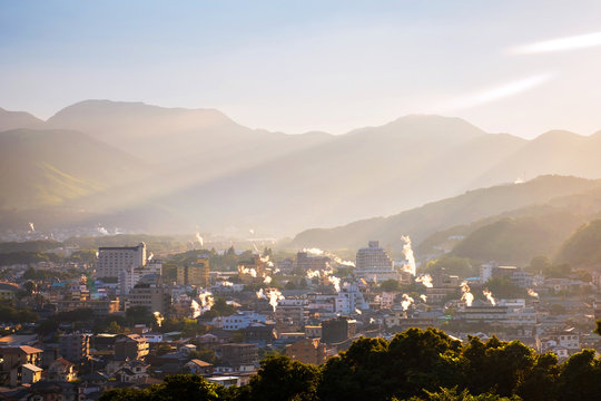 A sunset in a resort town of Beppu, Japan, with a view of mountains embracing the city and layers of sun.