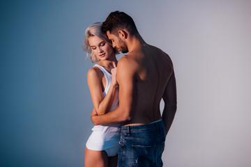 young heterosexual couple hugging on dark blue background Wall mural