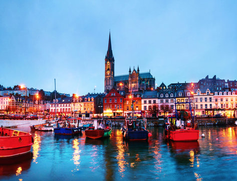 Port, houses, restaurants, shops, bars, pubs and Cathedral at night in Cobh, Ireland