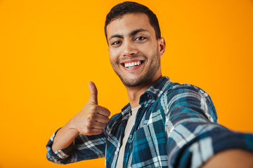 Cheerful young man wearing plaid shirt standing