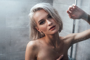 seductive young woman looking at camera and posing behind glass door while taking shower