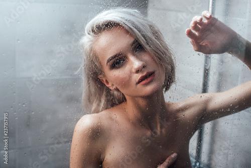 seductive young woman looking at camera and posing behind glass door ...