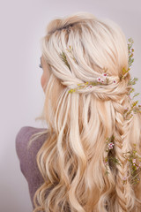 Back view of an elegant trendy hairstyle, interlacing curls and decorating with flower petals