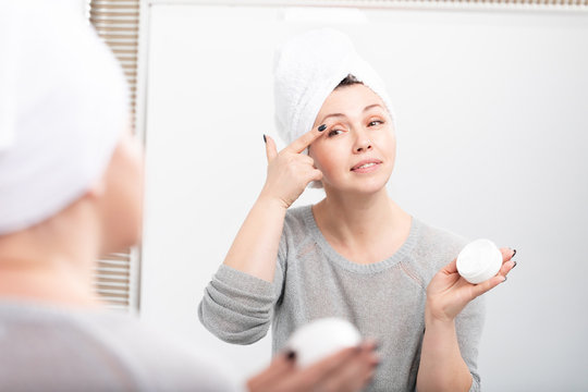 Smiling aged woman applying anti-aging cream. Happy mature woman using cosmetic cream to hide wrinkles.