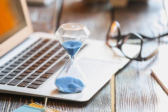 Hourglass on laptop keyboard. Time management concept