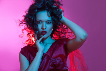 Femme fatale dancing, portrait in Studio with bright toning, blue and red color.