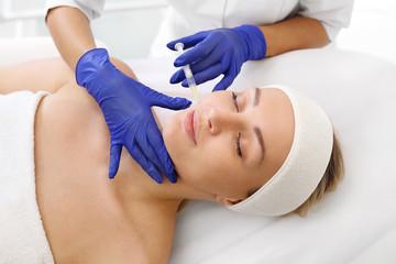 Fototapeta Wypełnianie zmarszczek kwasem hialuronowym. Pacjentka w klinice kosmetycznej, kosmetyczka wykonuje zabieg ostrzykiwania. obraz