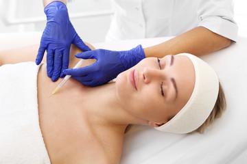 Lifting dekoltu. Ostrzykiwanie kwasem skóry. Pacjentka w klinice kosmetycznej, kosmetyczka wykonuje zabieg ostrzykiwania.