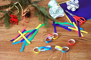 Making a garland from colored paper, step 2: sticking together colored paper strips into rings and joining them into a garland.