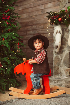 Cute sweet little boy is sitting on wooden rocking horse, wearing hat and checked shirt near big Christmas tree and fireplace