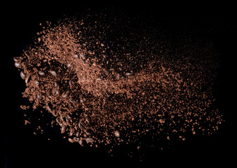 Coffee powder and coffee beans splash or explosion flying in the air