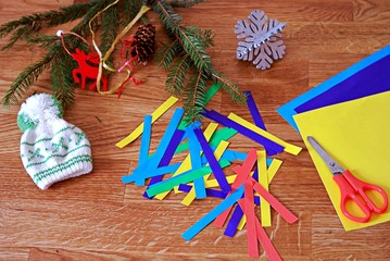 Making a garland of colored paper, step 1: cutting strips of colored paper. Children's DIY. Merry Christmas and New Year concept.