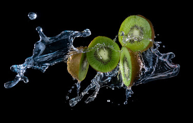 Kiwi fruit with water splash flying in the air isolated on black background