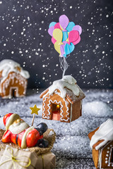 Gingerbread house on a festive Christmas snow background santa claus is relaxing on gifts while ginger house flying up with colorful balloons creativity snowing