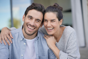 Portrait of very attractive couple smiling outside modern house