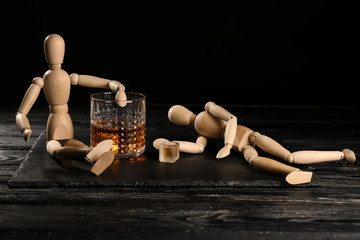Glass of whisky and two mannequins on wooden table against black background. Alcoholism concept