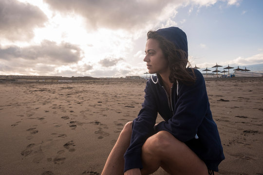 Lonely nice gurl witting at the beach in winter season with jacket looking in front - golden sunset and nobody in background - loneliness woman concept for young people who love to travel