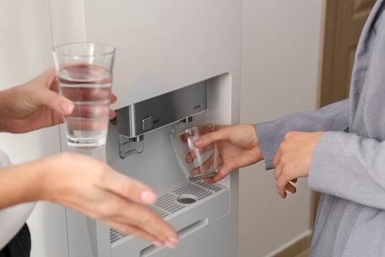 Women having break near water cooler in office