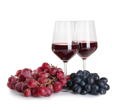 Glasses of red wine with ripe grapes on white background