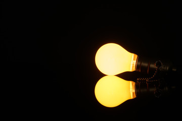 Glowing light bulb with reflection on black background