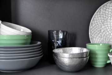 Set of clean tableware on shelf
