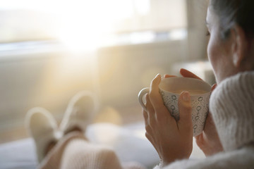 Obraz Cosy brunette at home on couch with hot drink - fototapety do salonu