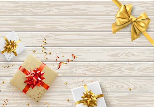 Festive wooden background with yellow satin bow and gifts.