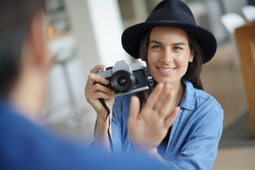 Trendy stunning brunette taking photos of model with vintage camera