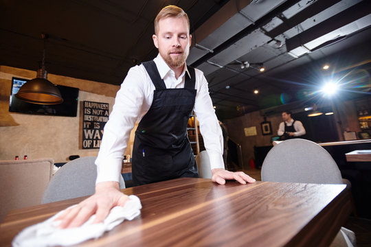 Content handsome young waiter with beard wearing white shirt and apron standing at wooden table and cleaning it with cloth in restaurant