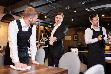 Serious displeased handsome young restaurant manager in formal jacket gesturing hand while giving task to waiter during cleanup