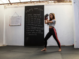 Thai transgender model wearing training boxing shield pads in a Thai Box (Muay Thai) gym in front of a blackboard with a work out list