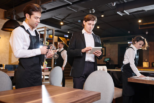 Serious concentrated handsome young restaurant manager using digital tablet while checking online records, waiting staff cleaning tables and crockery