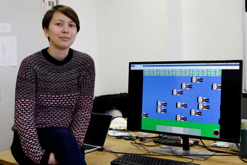 """Project manager Maja Cimerman of the """"Today is a new day"""" institute poses for a picture with a video game created to put players in the shoes of migrants on the Balkan route, in Ljubljana"""