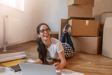 Young woman moving into a new house.She sitting on floor in empty apartment and calculate home budget.