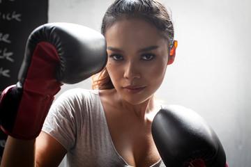 Thai transgender model in a Thai Box (Muay Thai) gym wearing boxing gloves