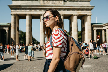 A tourist or a student with a backpack in Berlin in Germany visits the sights. Ahead is the...
