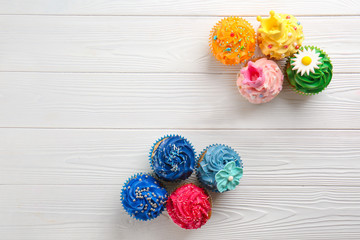 Composition with delicious colorful cupcakes on white wooden background