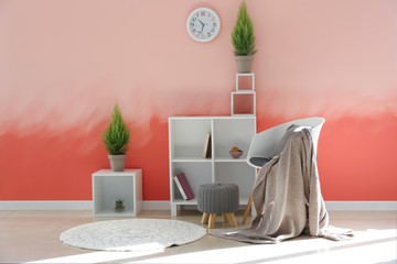 Interior of room with stylish furniture near pink wall