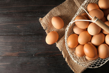 Basket with raw chicken eggs on dark wooden table